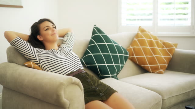Taking it easy on a sofa. Young woman walks to a sofa, sits down, smiles, she puts her hands behind her head and relaxes. resting stock videos & royalty-free footage