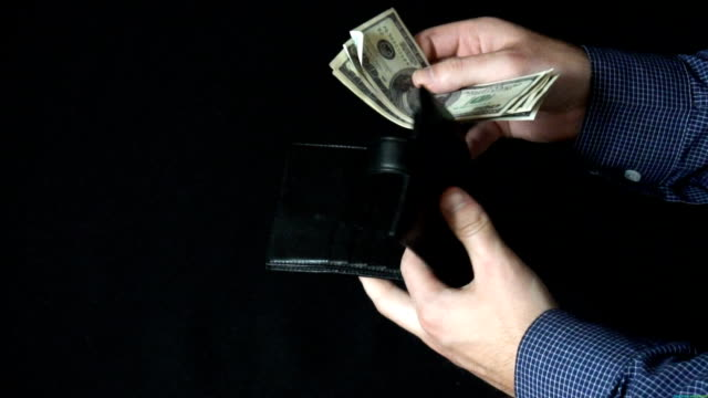 Taking Money Out of a wallet. The man opens a leather wallet and pulls out a 100 dollar bills video