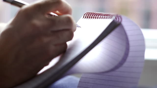 Taking notes on a ring binded notepad   INF
