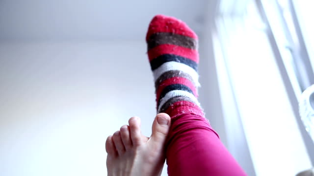 taking of the sock with left foot taking of red striped sock with left foot with only legs in the  frame  sock stock videos & royalty-free footage