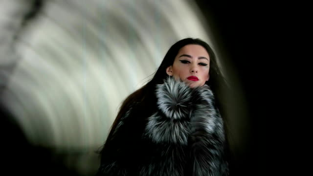 taking photo of beautiful long-haired girl wearing black and white fur coat through fan, red lips video
