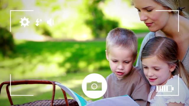 ta foton av en familj på en digitalkamera - digital reading child bildbanksvideor och videomaterial från bakom kulisserna