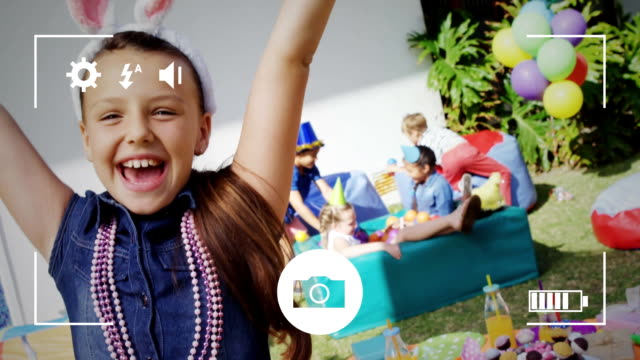 Taking photos of children at birthday party party on a digital camera Animation of a portrait of a pre teen Caucasian girl wearing bunny ears and smiling to camera at a birthday party with a group of children in the background, seen on a screen of a smartphone in picture mode with icons in the foreground dressing up stock videos & royalty-free footage