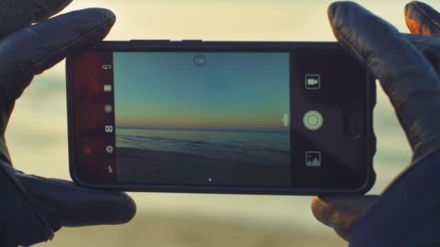 vidéos et rushes de prendre des photos de sunset sandy beach avec smartphone avec lens flare - photophone