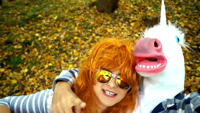 Taking selfie with unicorn Cheerful, redhead woman making faces and taking selfie with man masked into a unicorn in autumn park. mask disguise stock videos & royalty-free footage