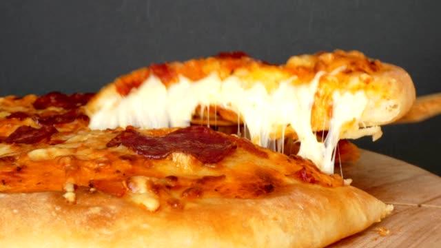 超伸縮性のあるチーズのピザのスライスを撮影 - チーズ 溶ける点の映像素材/bロール