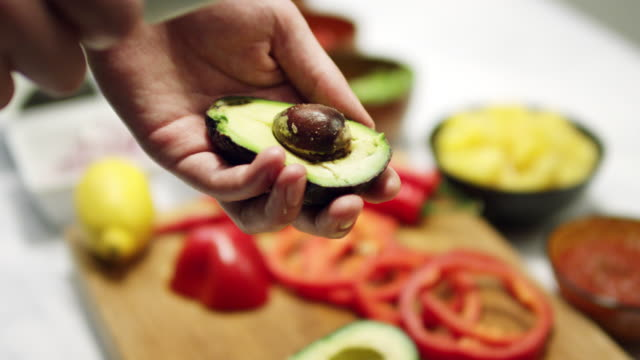 Taking the avocado nut out with a knife in slow motion video