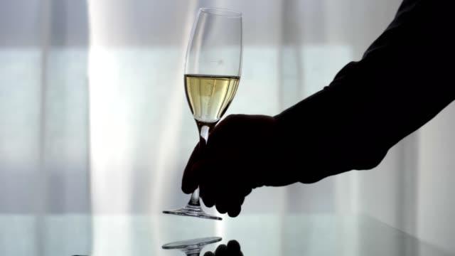 vidéos et rushes de prendre le verre de champagne du bureau réfléchissant contre le fond clair - flûte à champagne