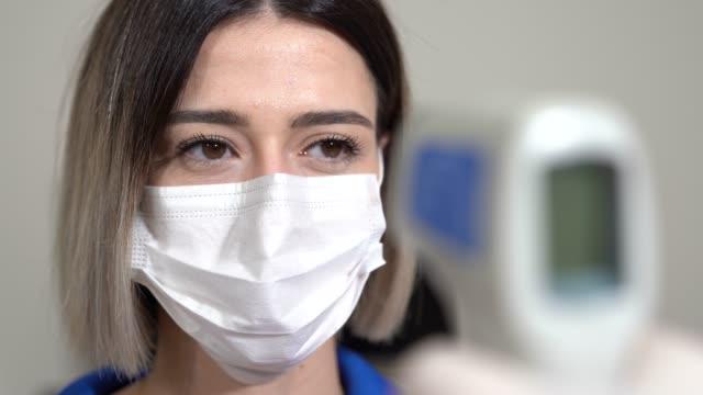 stockvideo's en b-roll-footage met het nemen van de temperatuur van de vrouw met thermometer te vinden besmet door coronavirus, covid-19. close-up schot. - thermometer