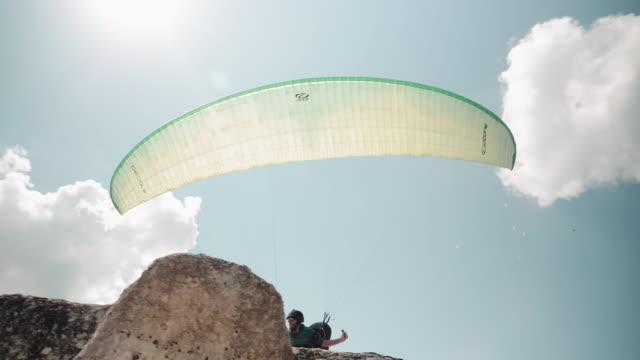 下から見たパラグライダーパイロットのws pov離陸、飛行、クロスカントリーパイロット、エクストリームスポーツ、冒険 - 斜めから見た図点の映像素材/bロール