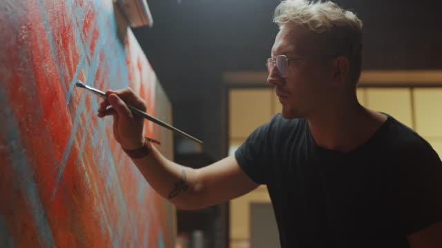 vidéos et rushes de artiste talentueux travaillant sur la peinture abstraite, trempe le pinceau dans la peinture et commence à dessiner l'art moderne audacieusement émotif. dark creative studio large canvas stands on easel illuminated dark creative studio large canvas stand - toile à peindre