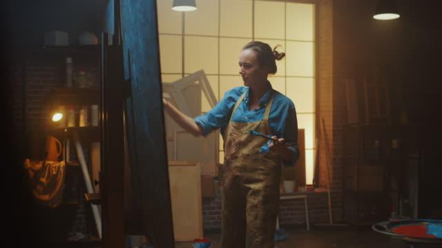 vidéos et rushes de artiste féminine talentueuse dessinant avec le pinceau énergiquement et avec enthousiasme, elle crée le chef-d'œuvre moderne de la peinture à l'huile. creative studio avec grande toile. side view arc shot - toile à peindre