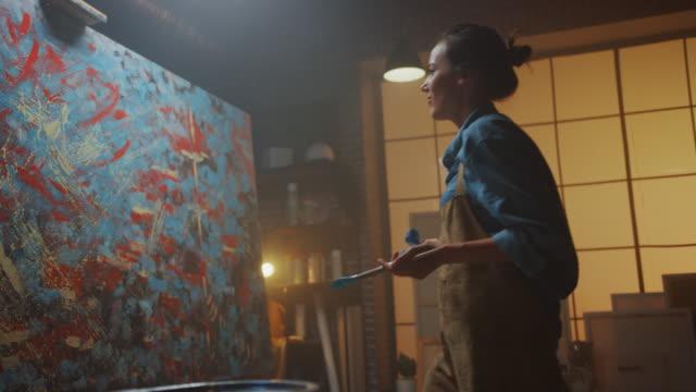 vidéos et rushes de artiste féminine talentueuse énergiquement et professionnellement utilisant le pinceau elle crée le chef-d'œuvre moderne de la peinture à l'huile. studio créatif avec grande toile de couleurs saisissantes. vue latérale à angle bas - peinture
