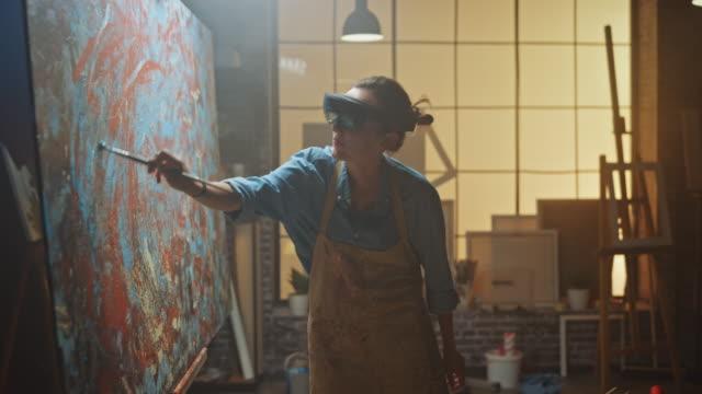 soyut boyama üzerinde çalışan artırılmış gerçeklik kulaklık giyen yetenekli kadın sanatçı, sanal gerçeklik arayüzünü kullanarak yeni konsept sanat yaratmak i̇çin boya fırçası kullanıyor. yüksek teknoloji creative modern studio - sanat, kültür ve eğlence stok videoları ve detay görüntü çekimi