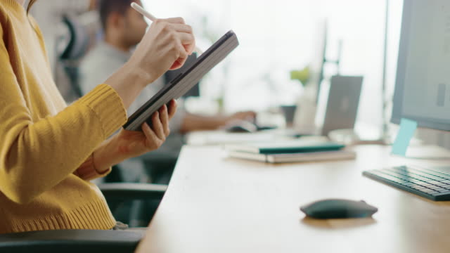 Talented Female Designer Sitting at Her Desk She's Drawing, Writing and Using Pen with Digital Tablet Computer. Focus on Hands with Pen. Bright Office where Diverse Team of Young Professionals Work