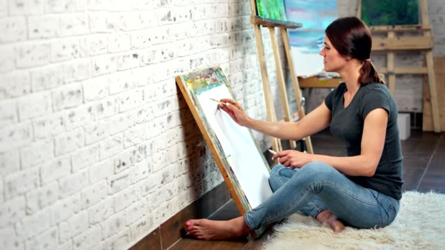 Talented female painter making graphic picture on canvas using pencil full shot