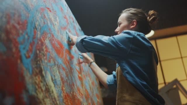 vidéos et rushes de talentueuse artiste féminine innovante dessine avec ses mains sur la grande toile, en utilisant des doigts, elle crée coloré, émotionnel, peinture à l'huile sensuelle. peintre contemporain créant l'art moderne abstrait - toile à peindre