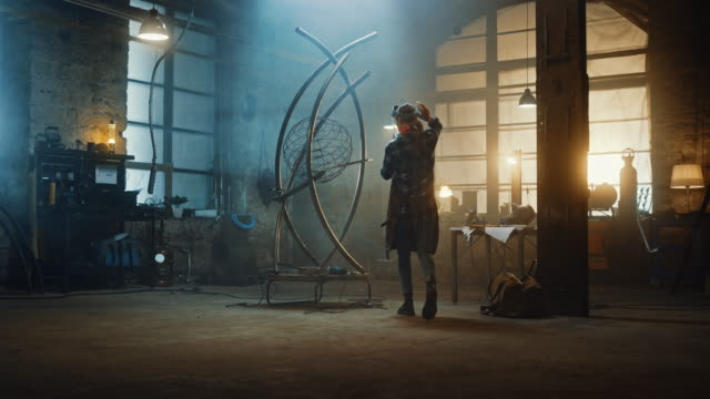 Talented Innovative Female Artist Walks Up to a Metal Tube Sculpture, Puts on a Safety Mask and Uses an Angle Grinder in a Workshop. Contemporary Fabricator Creating Modern Steel Art.