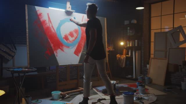 vidéos et rushes de artiste masculin talentueux travaillant sur une peinture abstraite, utilise le rouleau industriel pour créer l'image moderne audacieusement émotive. dark creative studio, large canvas stands on easel. zoom slow motion - toile à peindre