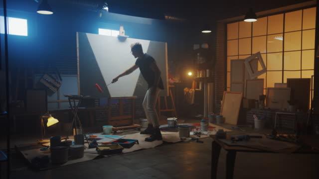 vidéos et rushes de artiste masculin talentueux travaillant sur une peinture abstraite, utilise le rouleau industriel pour peindre l'image moderne audacieusement émotive. dark creative studio large canvas stands on easel illuminated. ralenti - toile à peindre