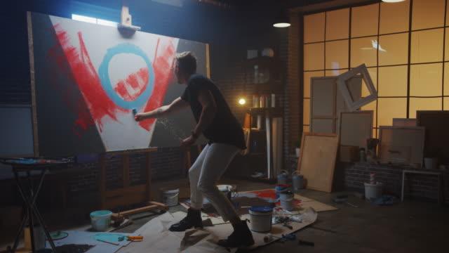 vidéos et rushes de artiste masculin talentueux travaillant sur une peinture abstraite, utilise le rouleau industriel pour créer l'image moderne audacieusement émotive. dark creative studio large canvas stands on easel. zoom slow motion - toile à peindre