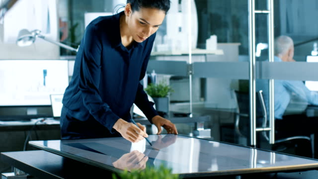 vídeos de stock e filmes b-roll de talented young female architectural designer draws building concept on a graphics tablet display. clean minimalistic office, concrete walls covered by blueprints. - ecrã tátil