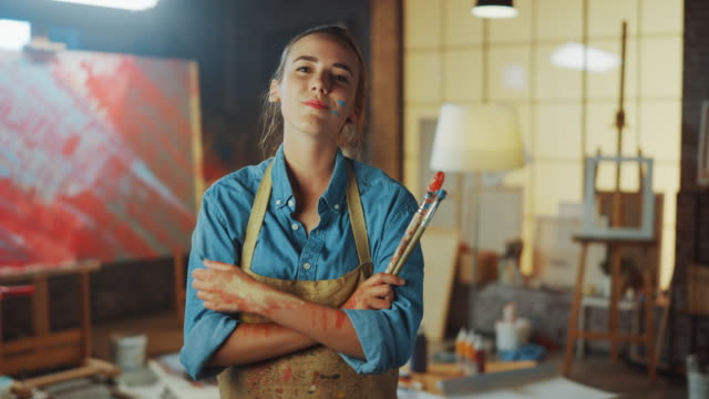 talented young female artist dirty with paint, wearing apron, crosses arms while holding brushes, looks at the camera with a smile. authentic creative studio with large canvas. face portrait - painter stock videos & royalty-free footage