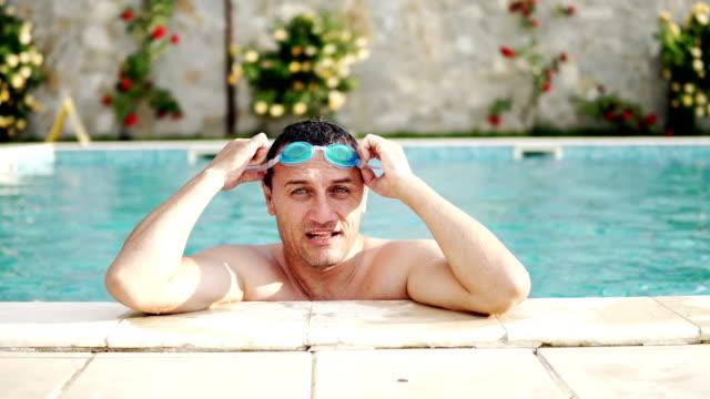 talking man with googles at luxury pool side, cinematic dof - google стоковые видео и кадры b-roll