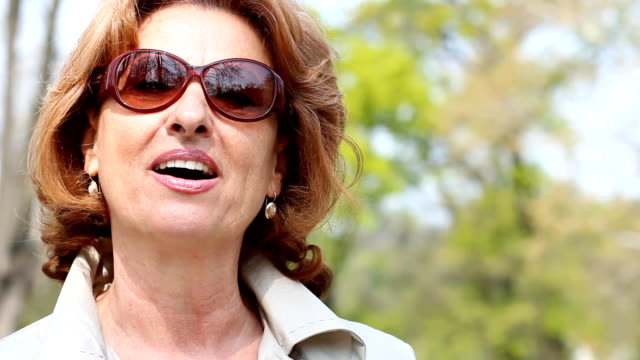 Talking mature woman Close-up of  mature woman talking  to camera outdoors. charming stock videos & royalty-free footage