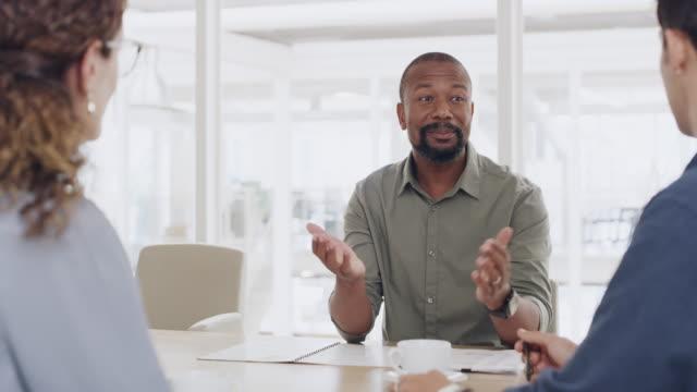stockvideo's en b-roll-footage met praten met zijn team over nieuwe strategieën - drie personen