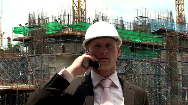 Talking A construction manager talks on his mobile. craftsman architecture stock videos & royalty-free footage