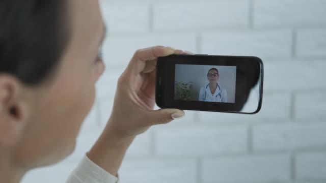 prata med en läkare på skype på en smartphone. - videor med medicinsk undersökning bildbanksvideor och videomaterial från bakom kulisserna