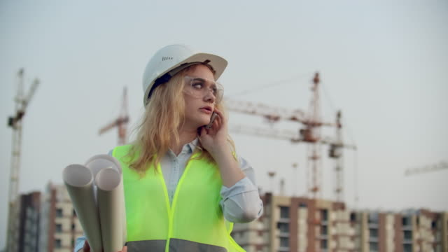 Talking woman in a helmet on the phone on the background of construction with cranes holding drawings in hand. Female engineer on construction site. Talking woman in a helmet on the phone on the background of construction with cranes holding drawings in hand. Female engineer on construction site civil engineering stock videos & royalty-free footage