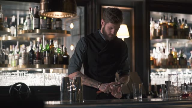 Tall bearded bartender crushing big piece of ice with the knife standing at the bar counter. video
