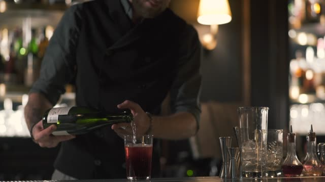 Tall bearded bartender pouring wine in the glass with ice. video