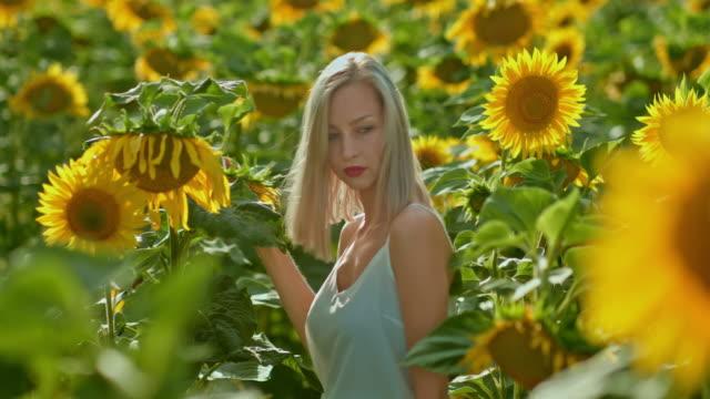 Tall blooming sunflowers, a beautiful girl walks across the field. Endless field of flowers, a romantic walk. Portrait view. 4k, 10bit, ProRes