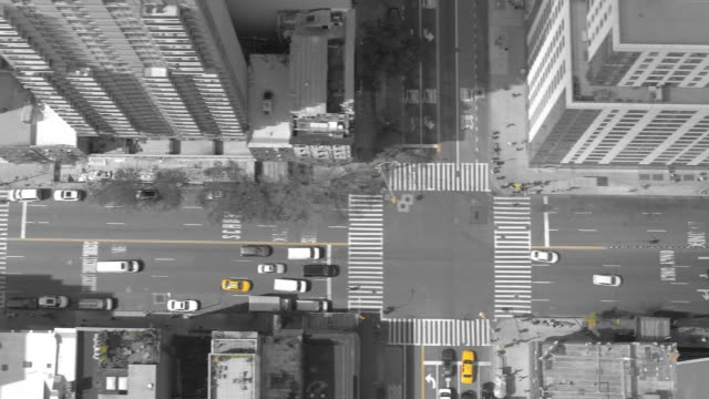 aerial top down: tall buildings surround busy city avenue filled with traffic. - black and white architecture stock videos & royalty-free footage