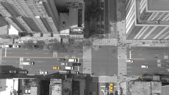 vidéos et rushes de antenne top-down: immeubles de grande hauteur entourent avenue ville animée, remplie de trafic. - image en noir et blanc