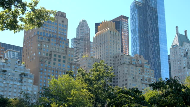 CLOSE UP: Tall glassy skyscrapers and luxury residential buildings in NY City LOW ANGLE VIEW, CLOSE UP: Highrise residential buildings, blocks of flats, luxury real estate, offices and modern glassy skyscrapers in Midtown Manhattan, New York City, view from the Central Park central park manhattan stock videos & royalty-free footage