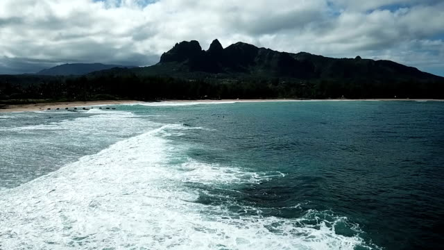 Tall Mountain Looming Over Cove and Waves Washing on Shore video