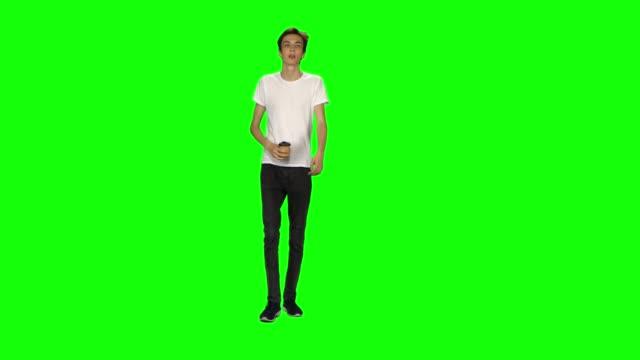 vídeos de stock e filmes b-roll de tall skinny teen guy calmly walking and drinking coffee on green screen background. chroma key, 4k shot. front view - teeshirt template