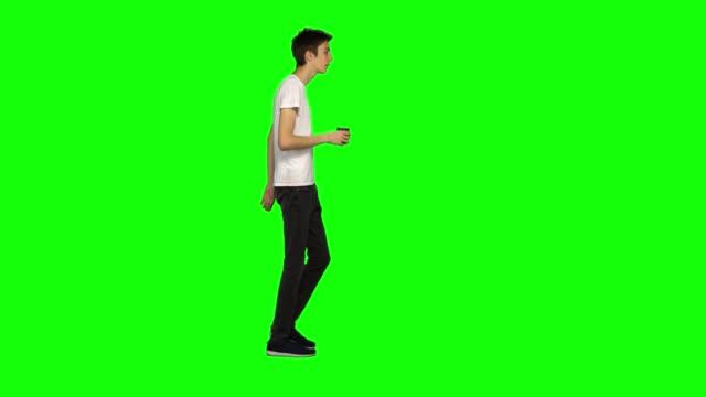 vídeos de stock e filmes b-roll de tall skinny teen guy calmly walking and drinking coffee on green screen background. chroma key, 4k shot. profile view - teeshirt template