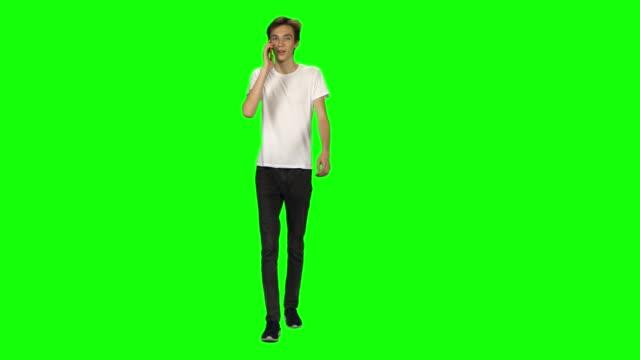 vídeos de stock e filmes b-roll de tall skinny teen guy calmly walking and talking on the mobile phone on green screen. chroma key, 4k shot. front view - teeshirt template