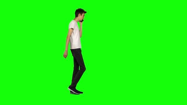 vídeos de stock e filmes b-roll de tall skinny teen guy calmly walking and talking on the mobile phone on green screen. chroma key, 4k shot. profile view - teeshirt template