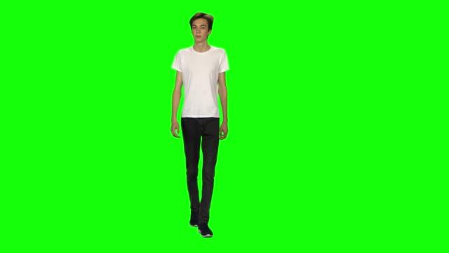 vídeos de stock e filmes b-roll de tall skinny teen guy calmly walking on green screen background. chroma key, 4k shot. front view - teeshirt template