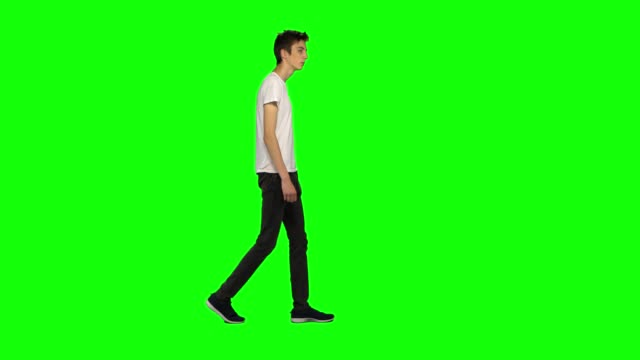 vídeos de stock e filmes b-roll de tall skinny teen guy calmly walking on green screen background. chroma key, 4k shot. profile view - teeshirt template