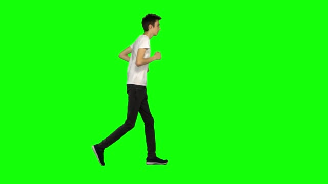 vídeos de stock e filmes b-roll de tall skinny teen guy is running on green screen background. chroma key, 4k shot. profile view - teeshirt template