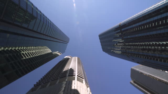 Tall skyscrapers spin quickly through the frame Tall city buildings in a downtown financial district spin quickly counter clockwise through the frame evoking a sense of corporations and markets spinning out of control in a stock market crash.  4K international architecture stock videos & royalty-free footage