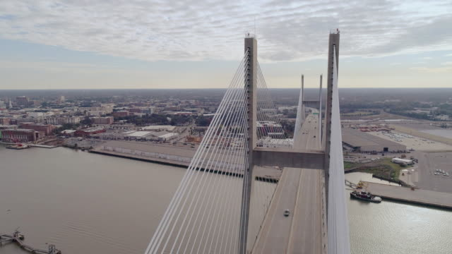 Talmadge Memorial Bridge over the Savannah River, with a view of Savannah in the backdrop, on the border between Georgia and South Carolina. Cloudy fall early evening. Aerial drone video with the panoramic camera motion. - vídeo