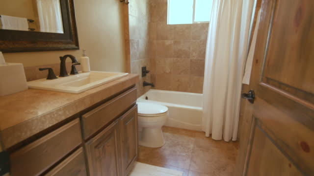 Tan Bathroom Rise from Doorway to Shower starts low on a modern bathroom and rises to the shower bathroom stock videos & royalty-free footage